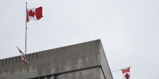 Flags fly over the Canadian Embassy in Washington, DC, October 22, 2014. Gunfire echoed through the Gothic...