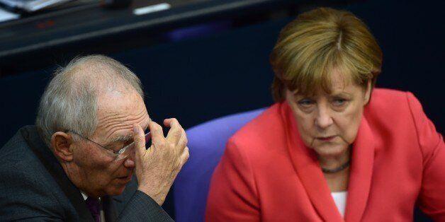 German Chancellor Angela Merkel (R) speaks with German Finance Minister Wolfgang Schaeuble before addressing...