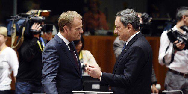 European Council president Donald Tusk (L), talks with European central bank president Mario Draghi,...