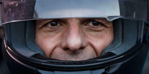 Greece's Finance Minister Yanis Varoufakis puts on his motorbike helmet as he leaves his office in Athens,...