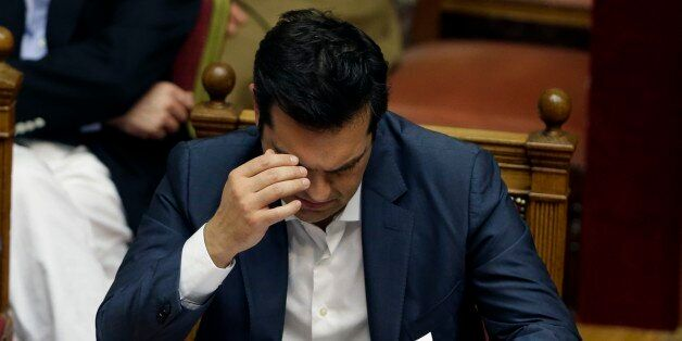 Greece's Prime Minister Alexis Tsipras reads his notes during a parliament meeting in Athens, Thursday,...