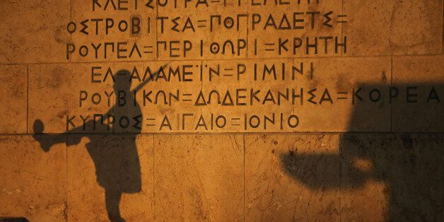 ATHENS, GREECE - JULY 13: The shadow of a Greek Presidental Evzoni guard falls on the parliament building...