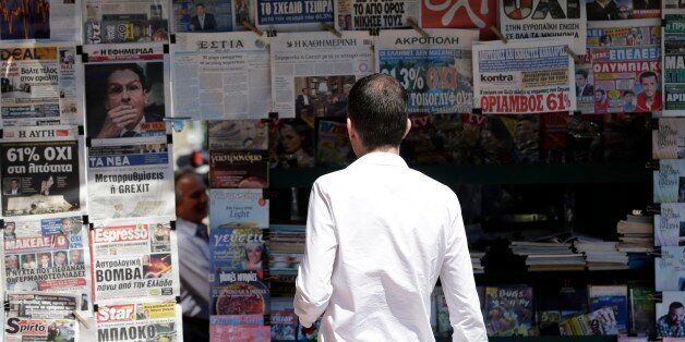 A man reads the front pages of the Greek newspapers in Athens, Monday, July 6, 2015. Greek Finance Minister...