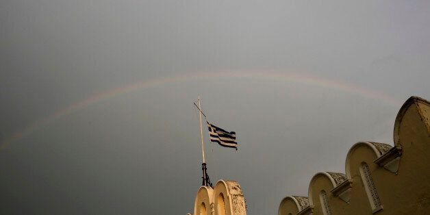 A Greek flag flies on top of the municipality market with rainbow on the background on Kos island, Greece,...