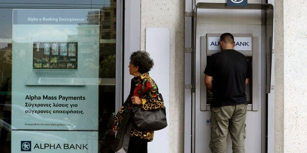 A man uses an ATM outside a bank in Athens, Friday, June 19, 2015. Several European countries said openly...