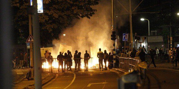 Protesters clash with riot police forces in The Hague's Schilderswijk district, the Netherlands, late...