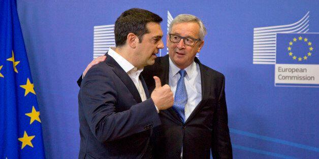 Greek Prime Minister Alexis Tsipras, left, speaks with European Commission President Jean-Claude Juncker...