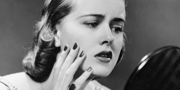 UNITED STATES - CIRCA 1950s:  Portrait of upset woman looking in hand mirror.