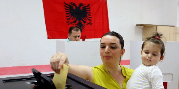 An Albanian casts her ballot for the local municipal elections, a key step in the country's efforts...