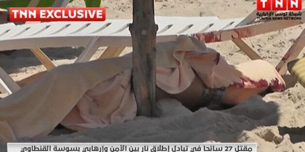 In this screen grab taken from video provided by TNN, a body is covered on a Tunisian beach, in Sousse,...