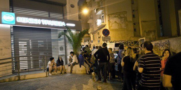Greek people queue in front of an ATM mache to withdraw cash from a National Bank of Greece in central...