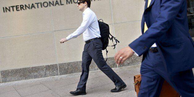 People walk past the headquarters of the International Monetary Fund June 30, 2015 in Washington, DC....