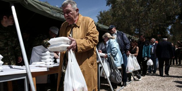 People line up to take a free meal which is distributed at a military camp in Athens, Sunday, April 12,...