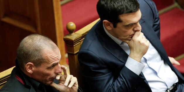 Greece's Prime Minister Alexis Tsipras, right, and Finance Minister Yanis Varoufakis gesture during a...
