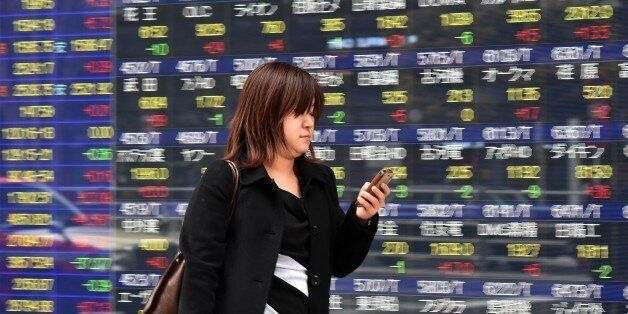 A woman uses her smart phone before a share prices board in Tokyo on April 9, 2015. Japan's share prices...