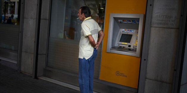 A man puts his wallet in his pocket after withdrawing euro notes from a bank machine in Athens, Thursday,...