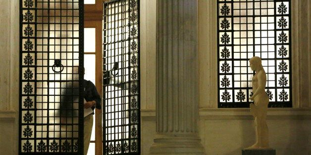 An unidentified man walks out of Maximos Mansion after Greek Prime Minister Alexis Tsipras announced...