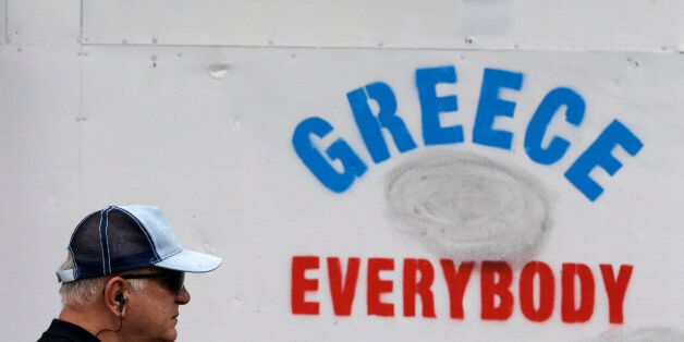 An elderly man passes a graffiti outside an old bank in Athens, Tuesday, June 30, 2015. Greek Finance...