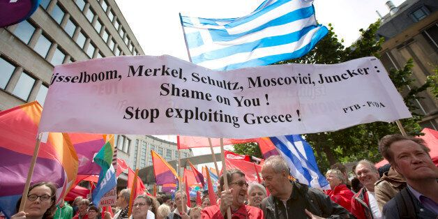 Demonstrators hold flags and banners during a protest march in solidarity with Greece in the center of...