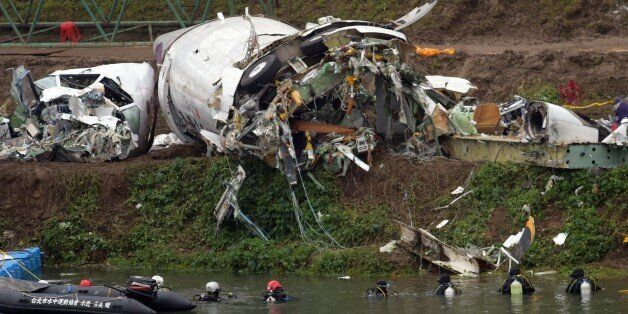 A general view shows divers searching the Keelung river for the remains of Transasia plane which crashed...