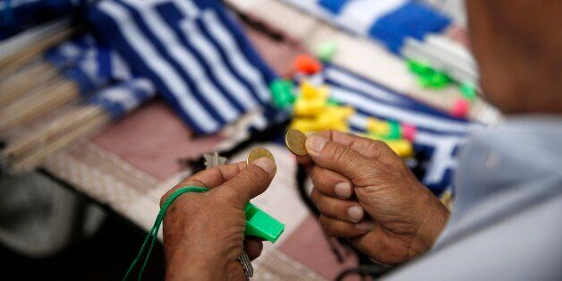 A man holds coins as he prepares to buy Greek flags during a rally organized by supporters of the YES...