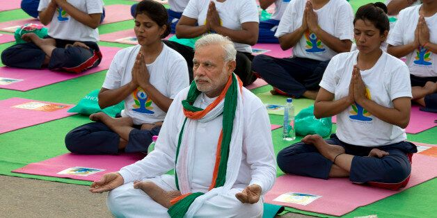 Indian Prime Minister Narendra Modi, center front, performs yoga along with thousands of Indians on Rajpath,...