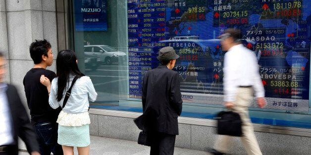 People look at an electronic stock indicator of a securities firm in Tokyo, Tuesday, June 23, 2015. Asian...