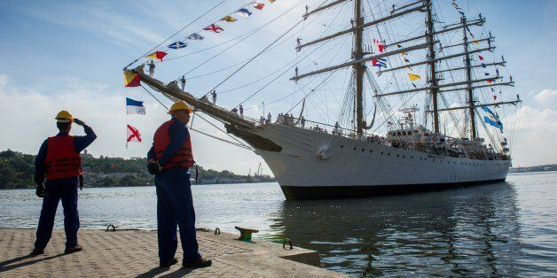 Cuban dockers stand by as the Libertad Argentine training sailing ship enters the port of Havana on July...