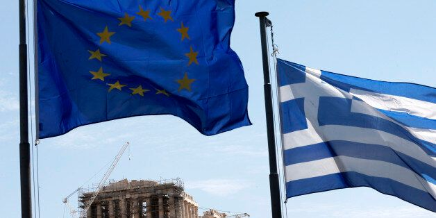 A Greek and a European Union flag billow in the wind as the ruins of the fifth century BC Parthenon temple...