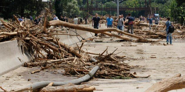 People walk around a damaged area near a flooded zoo in Tbilisi, Georgia, Sunday, June 14, 2015. Tigers,...