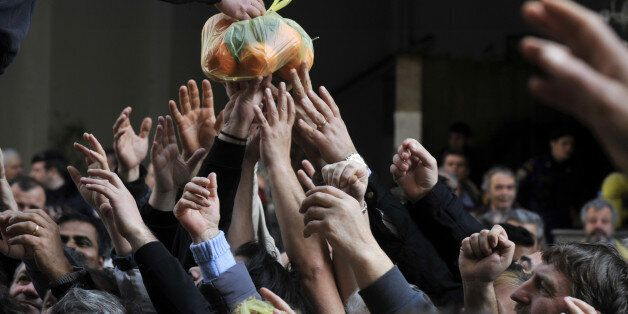 People reach out reach out for a bag of oranges during a free distribution of fruit and vegetables by...