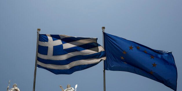 A Greek and a European Union flags flutter in front of statues of goddess Athena, left, and Nautilia,...