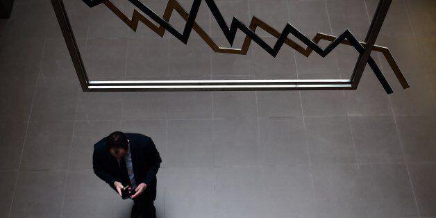 An employee walks at the Athens stock exchange on April 10, 2014. A milestone Greek bond sale, marking...