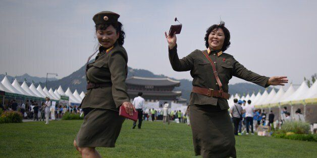 North Korean defectors wearing North Korean military uniforms dance in Gwanghwamun square during a 'unification...