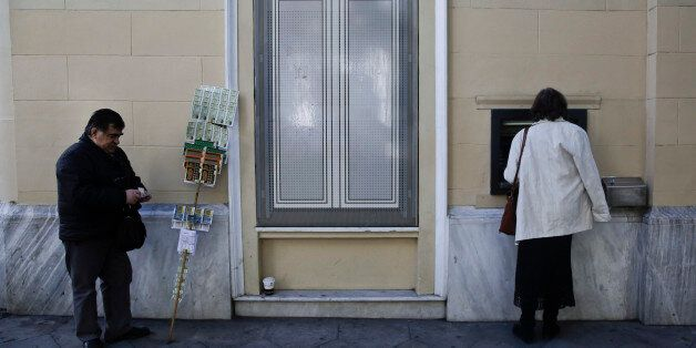A customer uses an ATM machine outside a bank as a street lottery vendor stands in central Athens, on...