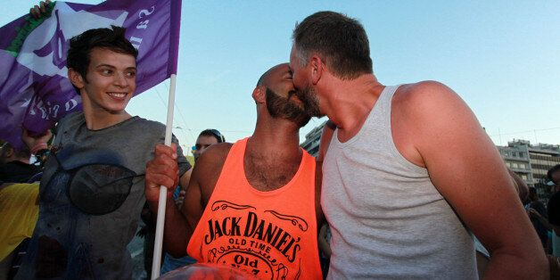 Two men kiss during the annual Gay Pride parade in Athens, Saturday, June 8, 2013. More than 1,000 people...