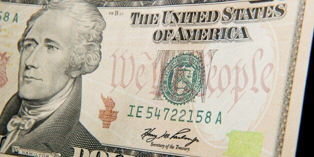 A close-up of the front of the US 10-dollar bill bearing the portrait of Alexander Hamilton, America's...