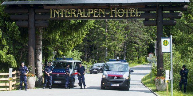 Policemen stand at a checkpoint on a road leading to the Interalpen-Hotel Tirol, venue of the Bilderberg...