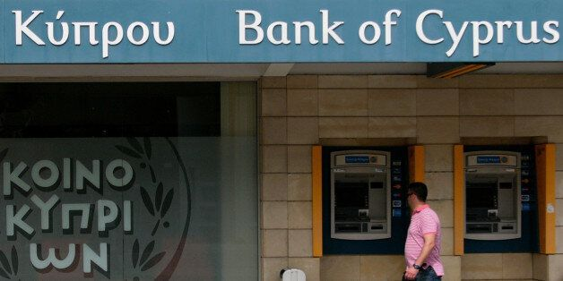 A man passes outside of a branch of bank of Cyprus at a main shopping street in central capital Nicosia,...