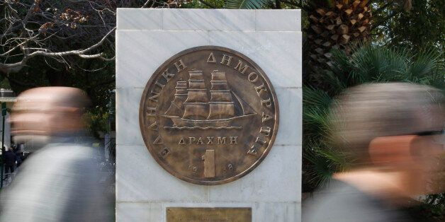 Pedestrians pass a plaque of a Greek one-drachma coin, which was replaced by the euro in 2002, outside...
