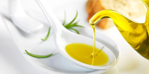 bottle pouring virgin olive oil in a porcelain
