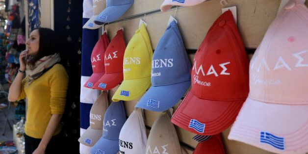 An employee of a tourist shop stands next to caps with the Greek flag in the traditional Plaka district...