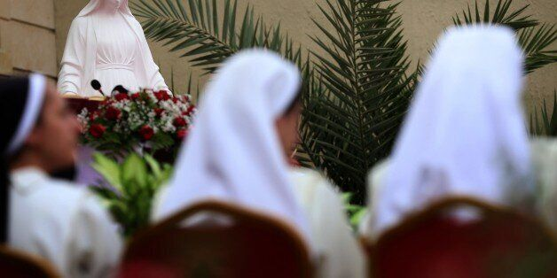 Nuns, along with Iraqi Christians who fled the violence in the northern Iraqi city of Mosul, attend a...