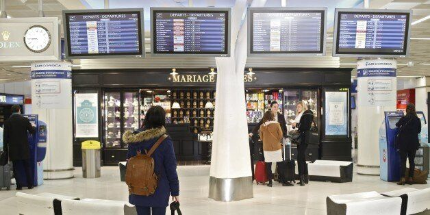 A passenger looks at departures boards, on April 8, 2015 at Orly airport, outside Paris, as hundreds...
