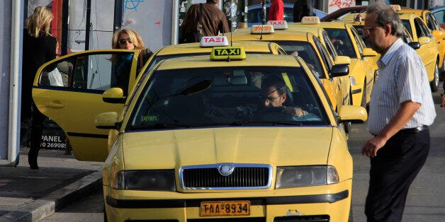Taxis wait for passengers during a 24-hour strike by metro, bus, trolley, and tram workers in Athens,...