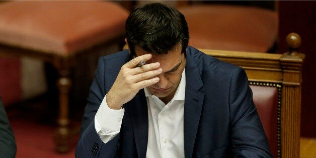 Greece's Prime Minister Alexis Tsipras checks his notes during an emergency Parliament session in Athens,...