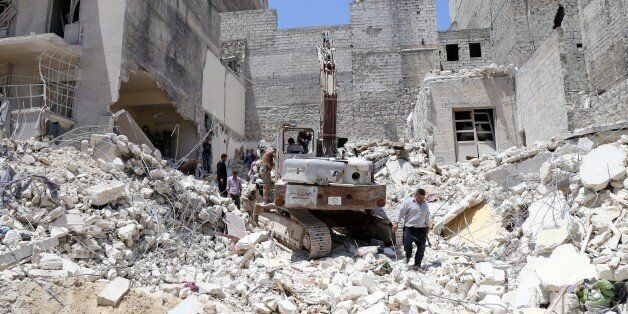 People inspect the rubble of collapsed buildings following a reported airstrike by government forces...
