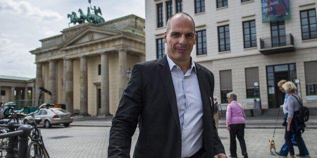 Greek Finance Minister Yanis Varoufakis walks across Pariser Platz in front of the landmark Brandenburger...