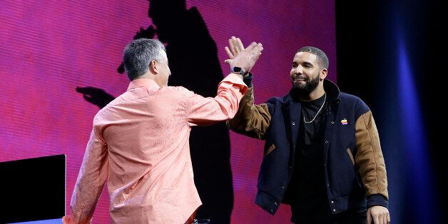 Musician Drake, right, high fives Eddy Cue, Apple senior vice president of Internet Software and Services,...