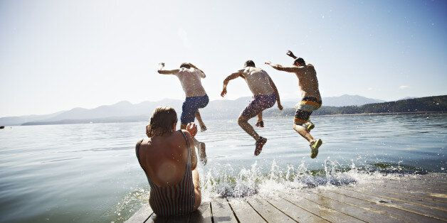 Woman sitting on the edge of floating dock while three men jump into water